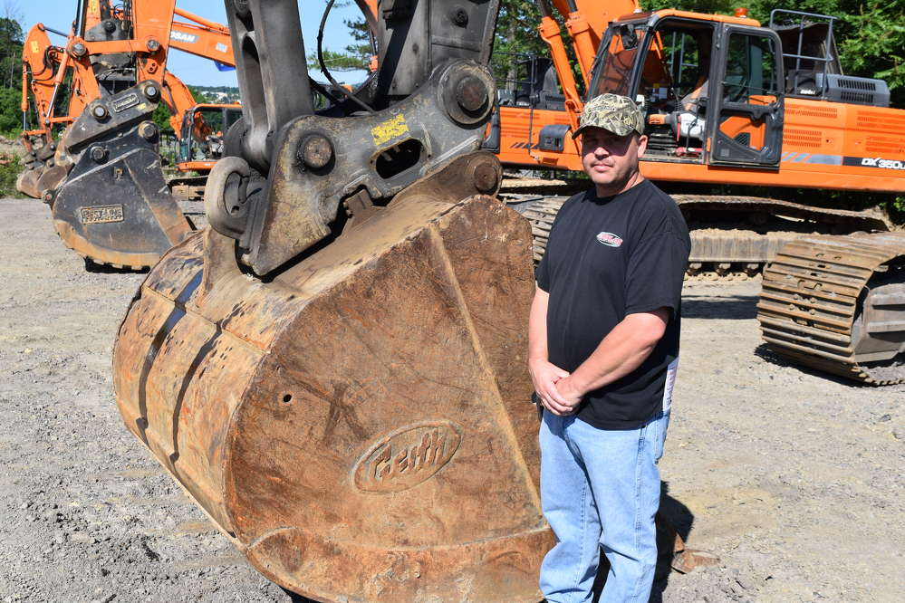 Adam Horwith, part owner of Horwith Leasing in Northampton, Pa., checks out the excavators during the auction.