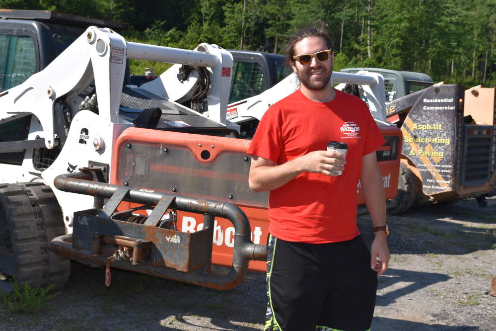 Zach Shumar, sales representative of Shumar Industries, Uniontown, Pa., takes a break from looking at some skid steers.
