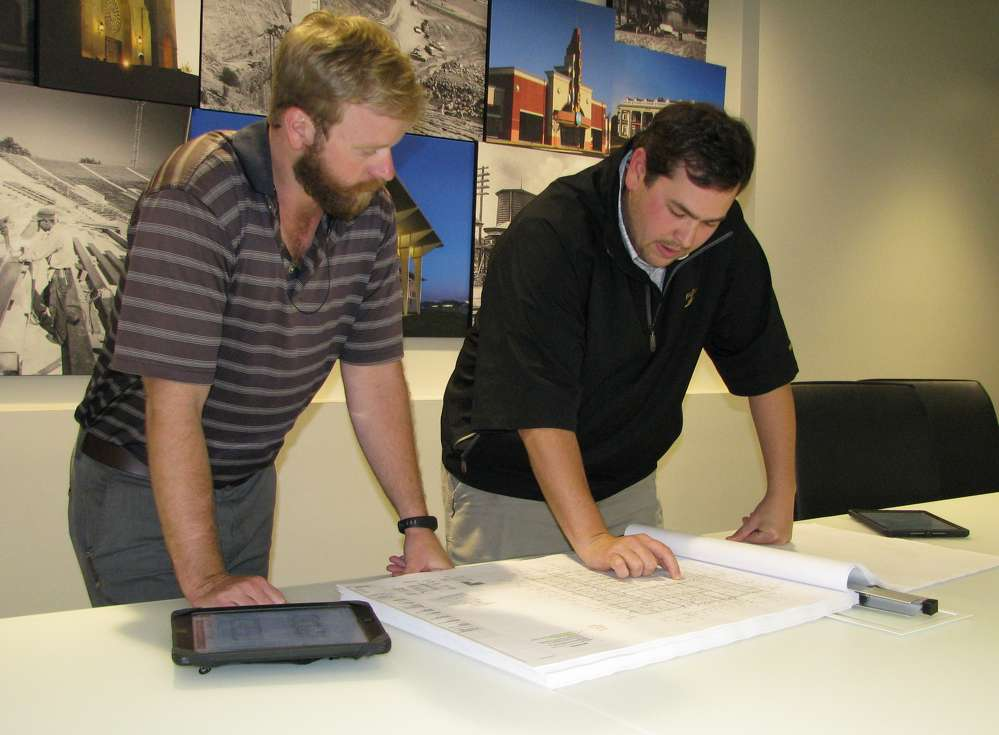 Chandler Gann (L) and Bill Plott, project engineers of Amason & Associates, Inc., look over plans for the Hub at Tuscaloosa project.