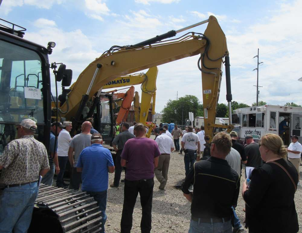 Auction attendees gather to bid on a strong selection of excavators at the sale.