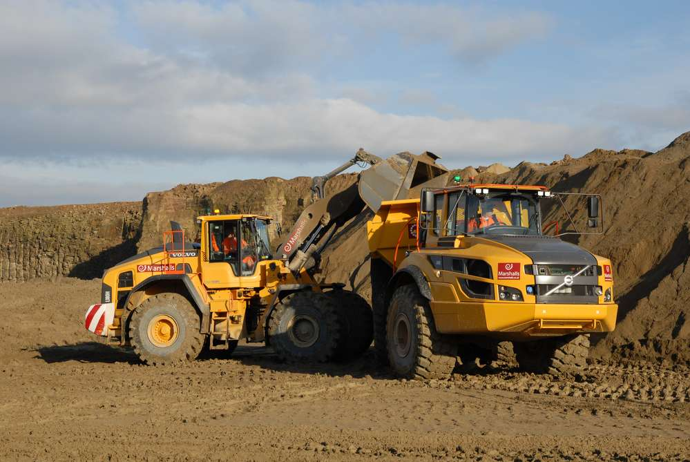 Marshalls' Volvo L180H wheel loader uses its lifting forces to unload earth into the A40G articulated hauler.