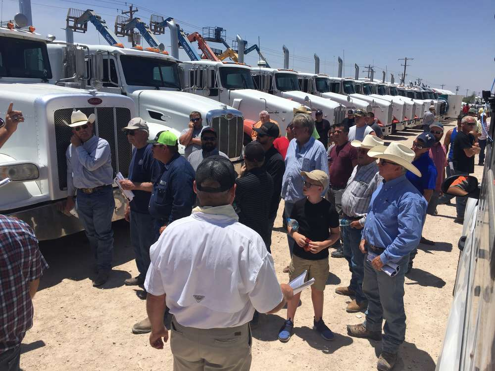 Customers wait to place their bids on a lineup of truck tractors sold absolute on June 21 at Jeff Martin Auctioneers' Stanton sale.