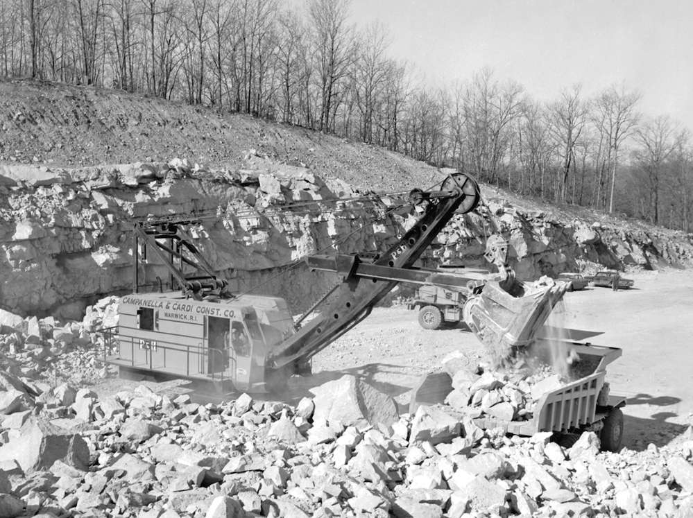 A Campanella & Cardi P&H 1055 shovel loads blasted rock into a Mack LYSW end dump truck on the big I-95 project in Groton. A Mack LVX end dump is waiting to be loaded. The photo was taken on March 29, 1963. The contractors owned 16 of the Mack LVX trucks. The first group of Mack M- 30X trucks purchased began to appear on this job.