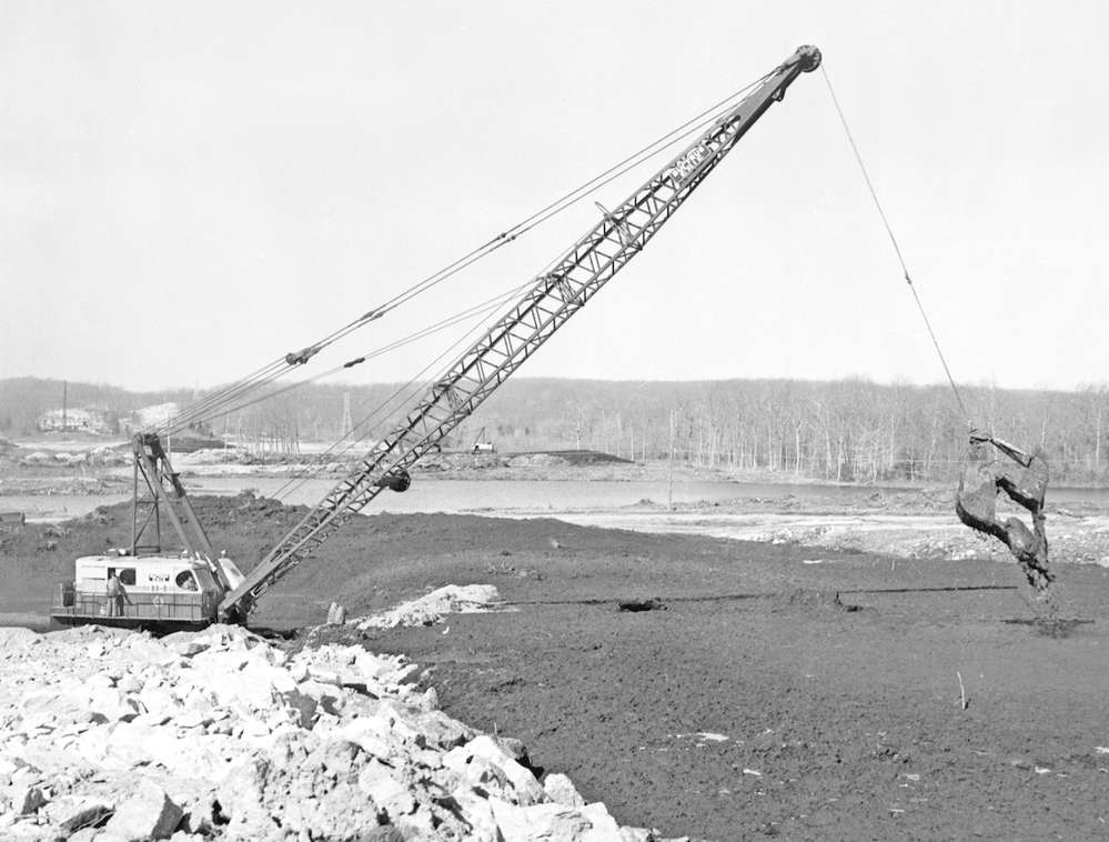 A Bucyrus-Erie 88-B equipped with a clamshell bucket is casting peat ahead of the broken rock fill on March 29, 1963. Campanella & Cardi may well have pioneered this practice. A dragline bucket, commonly used to excavate peat, unloads at or near the plumb point with the boom tip sheaves. Casting with a clamshell bucket increased your working range by an additional 20 to 30 ft. or more-eliminating a considerable amount of re-handling.