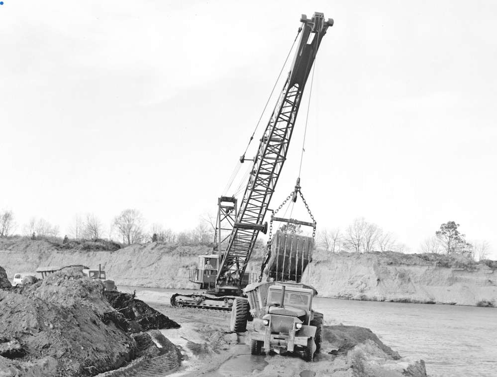 A Bucyrus-Erie 88-B equipped with a dragline bucket was loading borrow into a fleet of Euclid bottom dumps. The material was obtained from the Groton Reservoir, thereby increasing its capacity. The photo was taken Oct. 30, 1963.