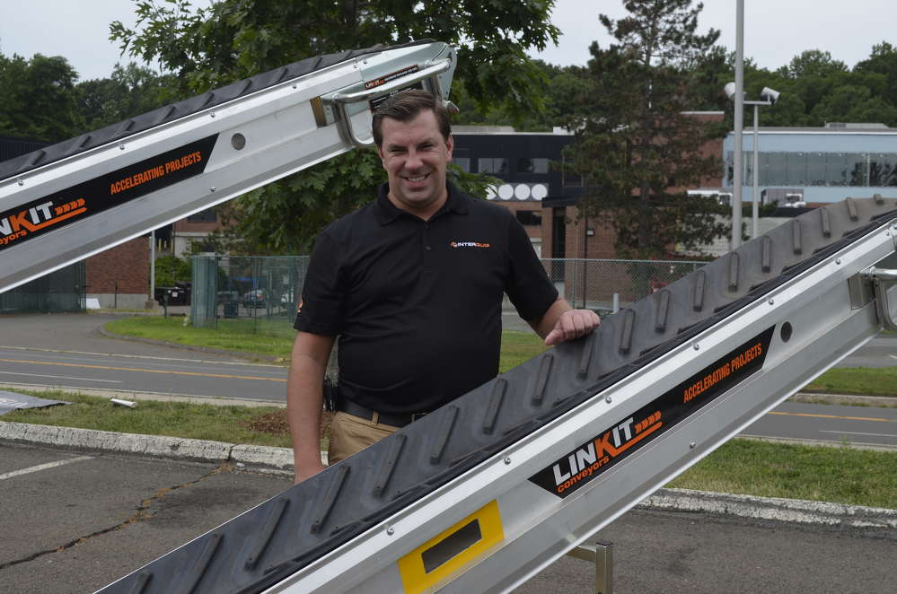 """Christopher Storr demonstrates the flexibility and convenience of the LINKIT """"Plug-N-Play"""" portable conveyors."""