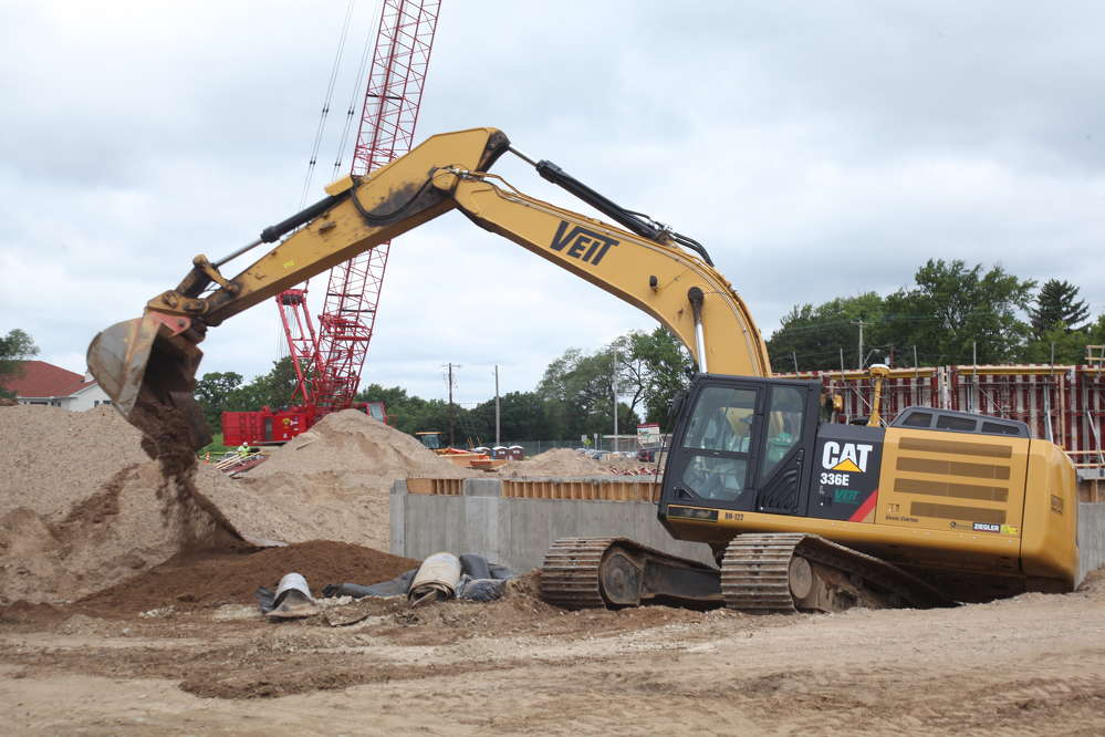 The operator of this Cat 336E excavator digs outside the building foundation.