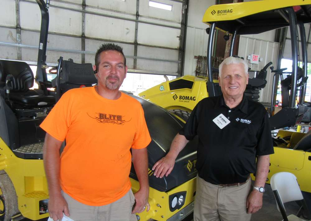 Joe Jones (L) of Elite Asphalt speaks with Dale Alferink, Bomag territory manager, about adding another Bomag to his fleet.