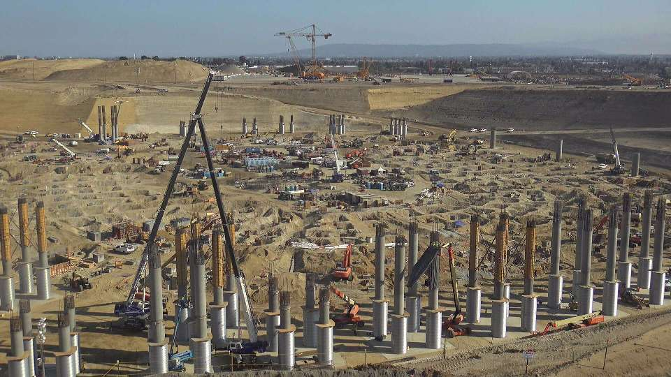 Most excavation at the project site has been completed and crews are constructing huge concrete pillars that will support the stadium structure.