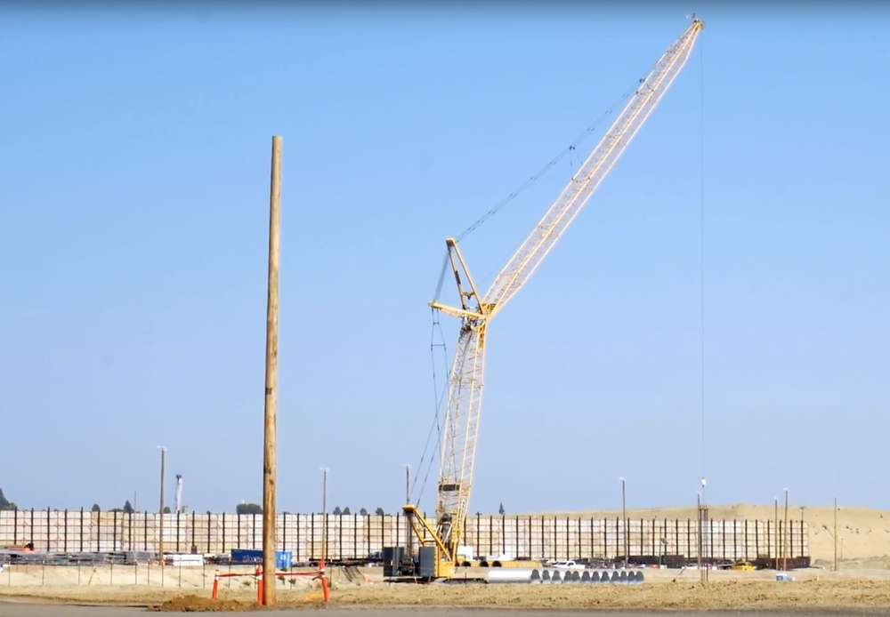 The giant cranes are used to install pilings for the stadium's foundation.