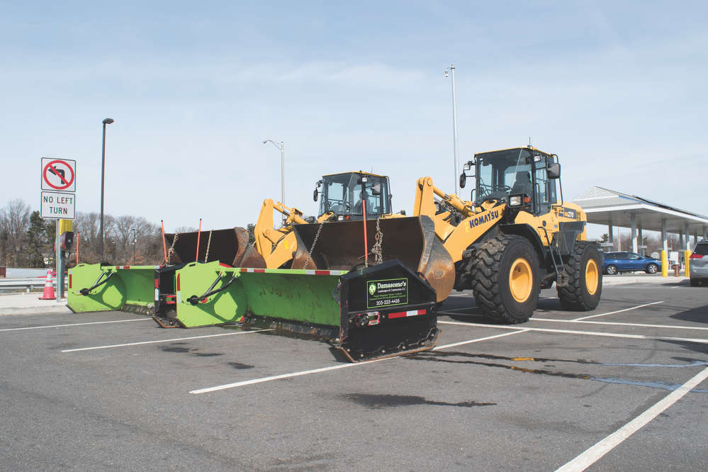 A pair of Komatsu wheel loaders wait for snow to fall at one of the three Interstate 95 exit-service-centers that Damasceno's Landscapes & Construction maintains throughout the winter.