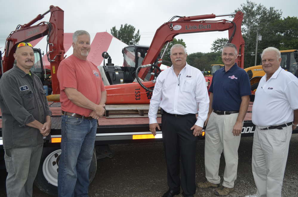 Representatives of the Genesee County Highway Department review the workings and benefits of an Allied Rammer hammer.