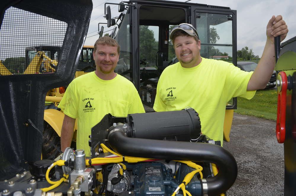 Shane McDevitt (L) and Ryan Hatch of the town of Portville check out the latest Bomag compact double drum roller.