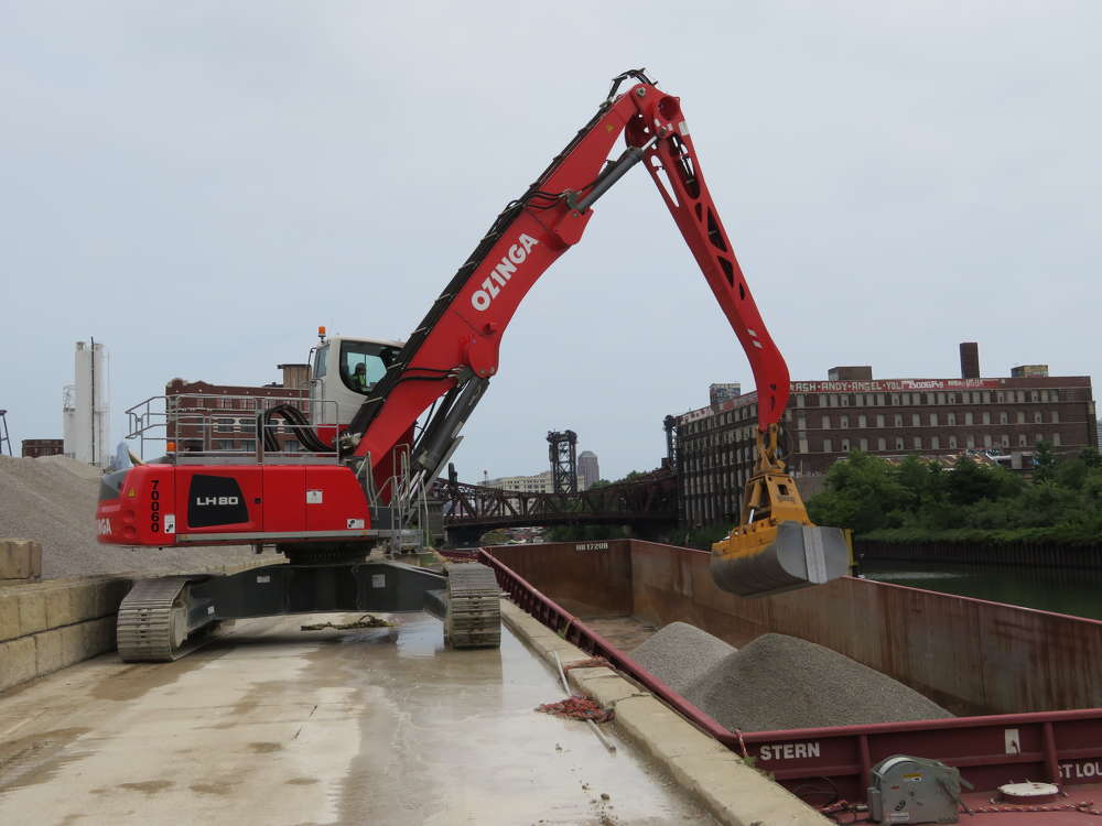The operator of the Liebherr LH-80 material handler unloads  a barge on the Chicago river.