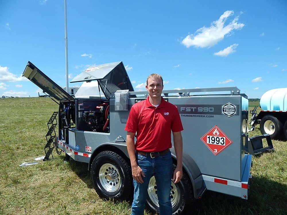 Derek Shalla, equipment sales representative, Stutsman Equipment Sales, Hills, Iowa, stands with the Thunder Creek FST 990 fuel, service and lubrication trailer.