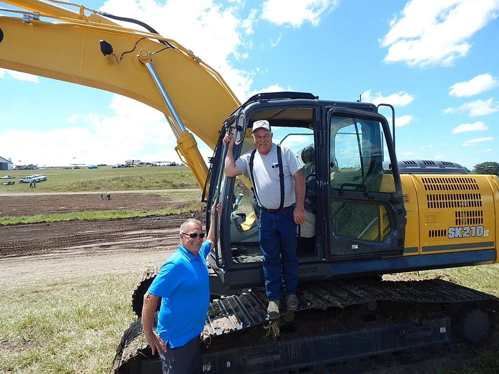 Mark Swedlund (L), co-owner of Mid Country Machinery, Fort Dodge, Iowa, shares a laugh with his customer, Jerry Eshelman of Eshelman Trenching, Greenfield, Iowa, after Eshelman demoed this Kobelco SK210.