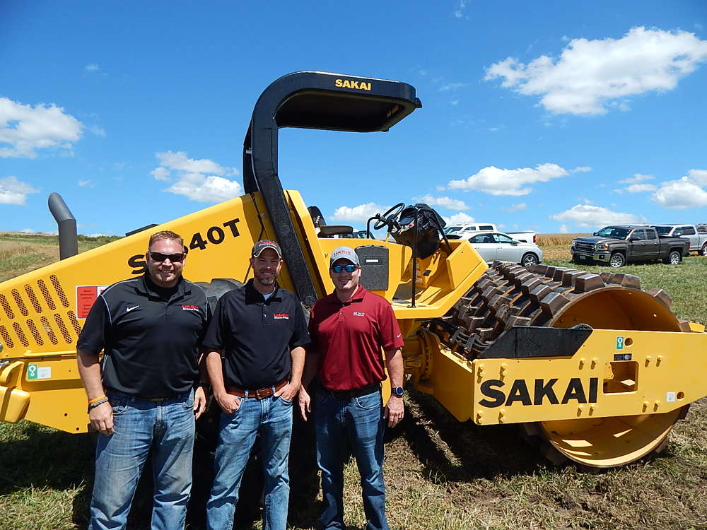(L-R): Dave Suther and Scott Bauercamper, territory managers, Rexco Equipment, and Josh Bottelman, president of Rexco Equipment, go over the features and benefits of a Sakai SV540T single padfoot drum vibratory compactor.