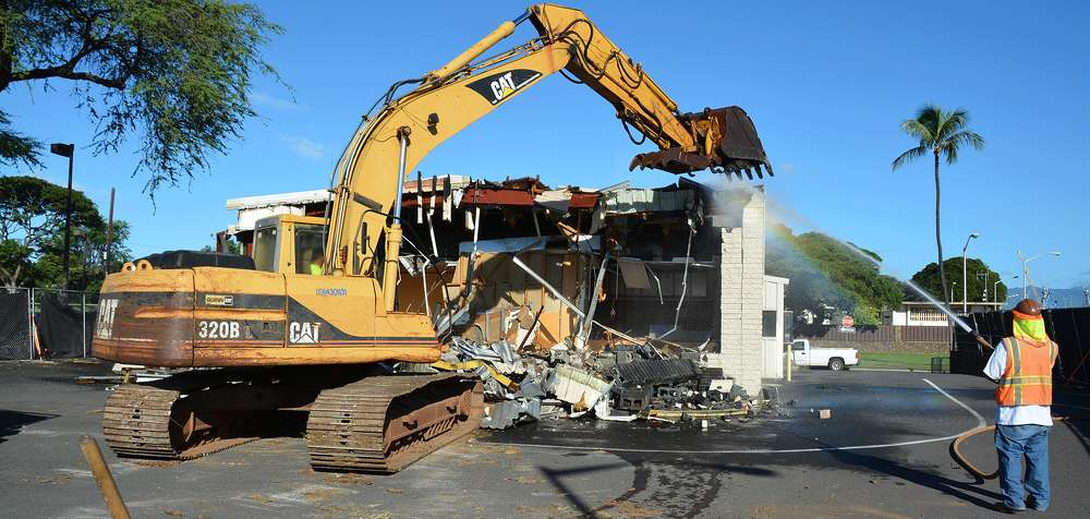 A Navy demolition crew removes a 1970's metal-framed building from Joint Base Pearl Harbor-Hickam facility inventory. Building debris was segregated for recovery of recyclable materials.