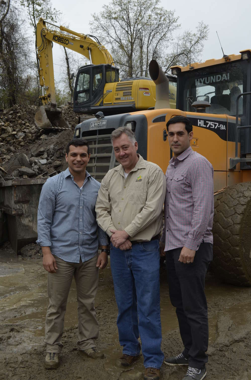 With their recently purchased Hyundai 757-9, (L-R) are Vito Secchiano, partner, Metro Green; Gary Wade, president of All Island Equipment; and Angelo Maiorano, partner, Metro Green.