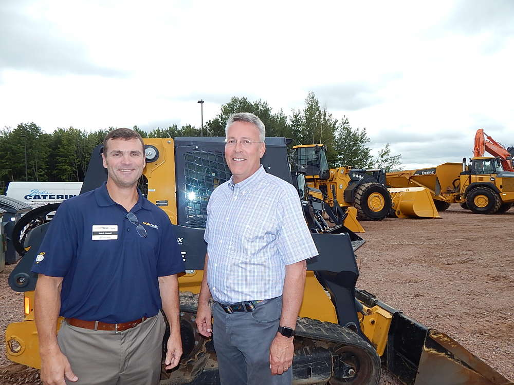 Dale Gessell, vice president and general manager of Nortrax, Grand Rapids, Minn., talks with Carl Lockhart, John Deere forestry sales manager, Ontonagon, Mich.