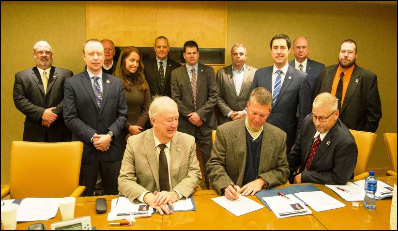 President Todd Young signs the resolution as the OAIMA Board and Senator Frank LaRose look on.