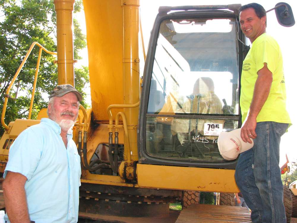 Lamar Chandler (L) and Kebo Almond, electrical contractors from Athens, Ga., show interest in bidding on John Deere 330CLC excavators.