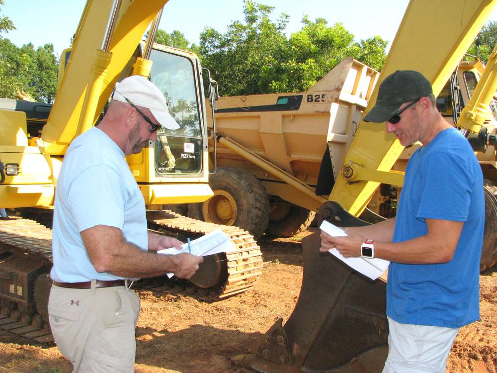 Chuck Spooner (L), Central Atlanta Tractor, Austell, Ga., and Jeff Bullock of JB Earthmoving Equipment, Atlanta, Ga., look over the lineup of machines in the sale.