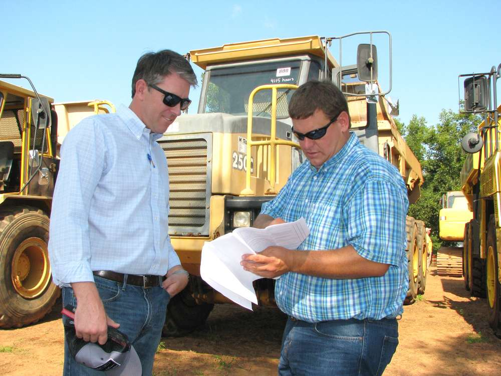 Cowin Equipment Company's Andrew Bell (L) and Chad Rich, Ricky Rich Backhoe & Grading, Blairsville, Ga., search for bargains at the auction.