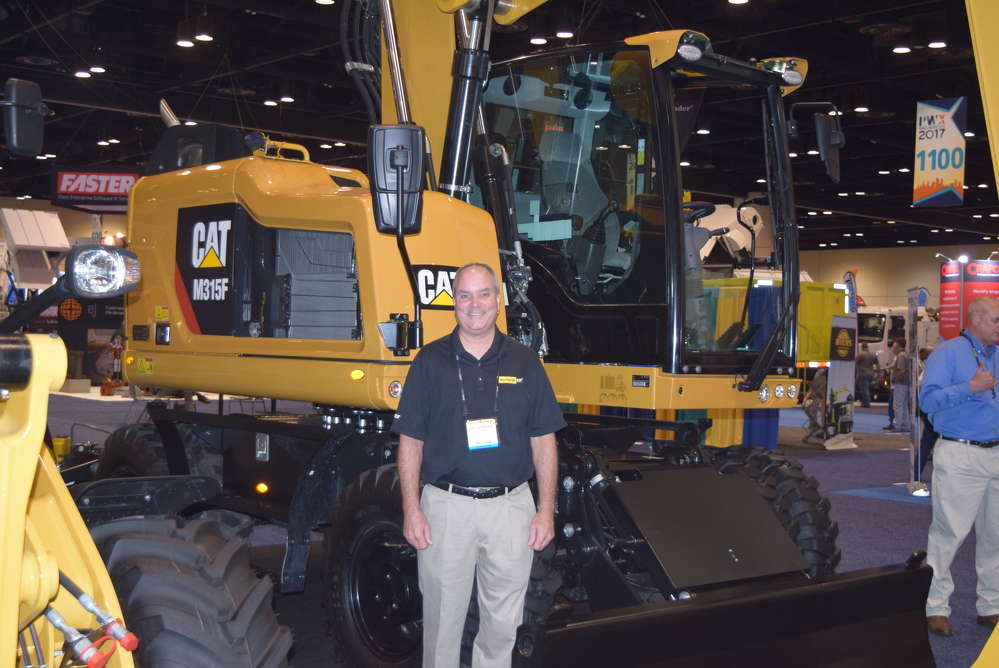 Greg Bennett, government sales, Kelly Tractor, stands in front of this Cat M315F.