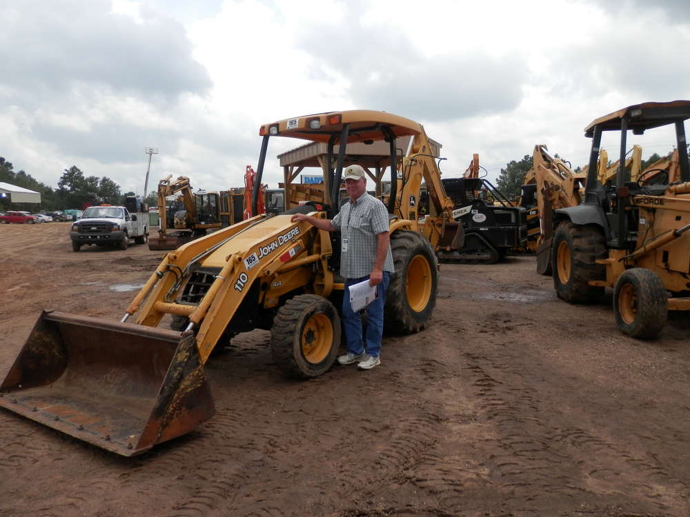Dennis Kendrick from Wiggins, Miss., stands with a 2002 John Deere 110 4x4 loader backhoe that was sold in Brooklyn, Miss.