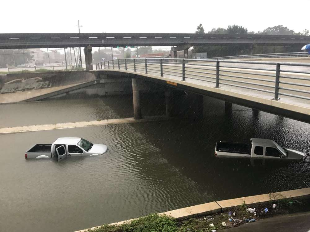 Vehicles sit half submerged in flood waters under a bridge in the aftermath of Hurricane Harvey in Houston. 