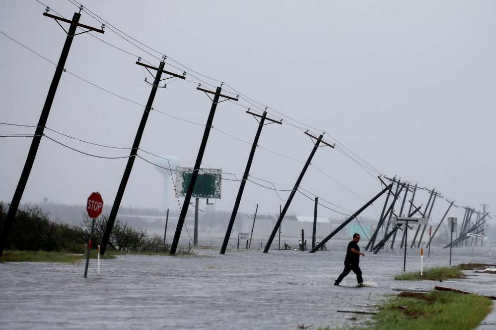 A man walks through floods waters and onto the main road Aug. 26 after surveying his property, which was hit by Hurricane Harvey in Rockport, Texas. 