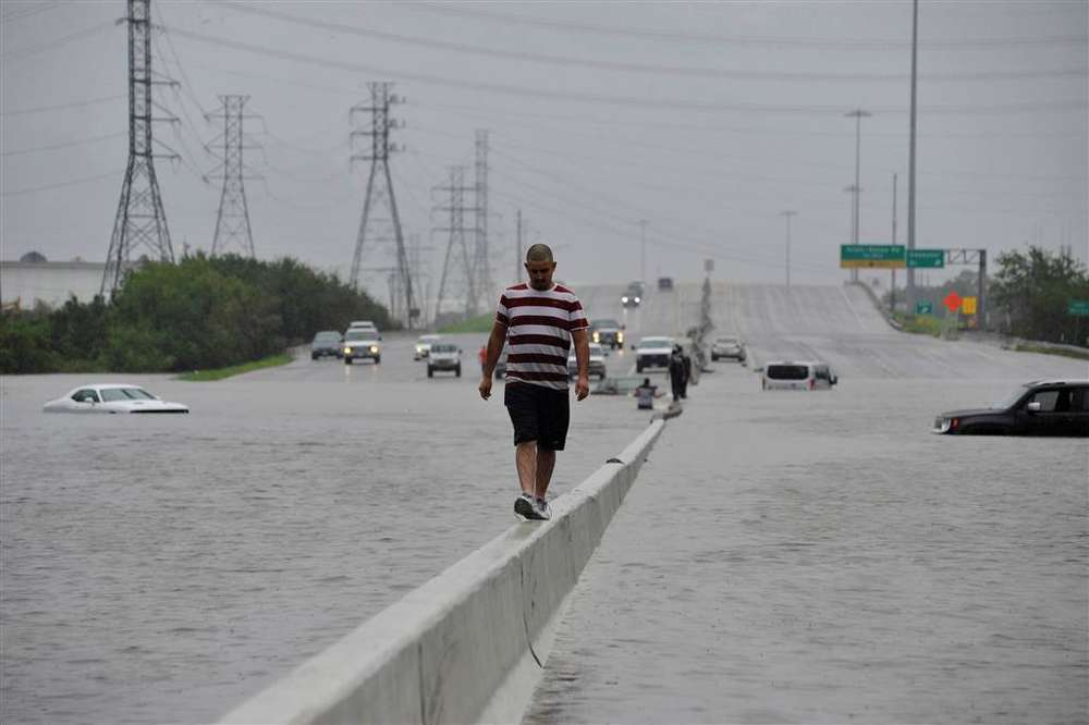 A stranded motorist escapes floodwaters along Interstate 225 on Aug. 27, after Hurricane Harvey inundated the Texas Gulf coast with rain causing life-threatening flooding. 