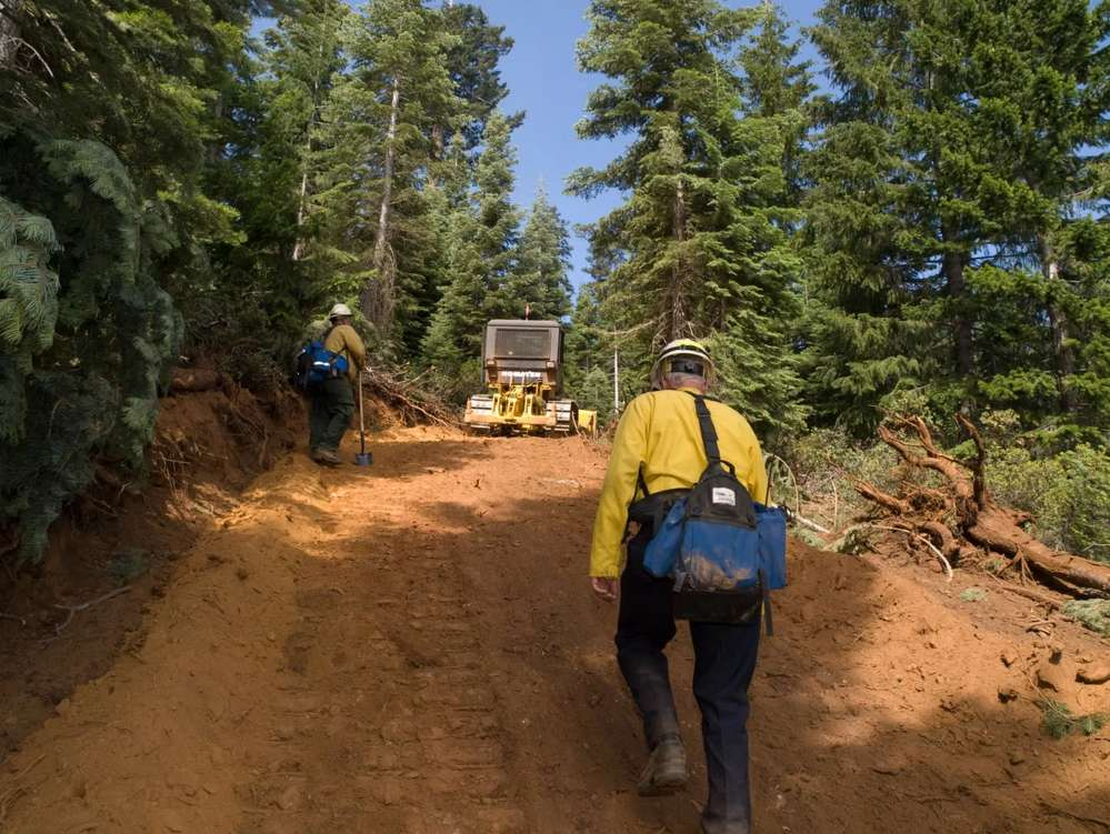 """""""They'll take the dozer out and drive alongside the fire or get ahead of it if possible and make a large line of dirt around it and when the fire hits that dirt, it goes out,"""" said Jessica Gardetto, spokesman for the National Interagency Fire Center. (National Interagency Fire Center photo)"""