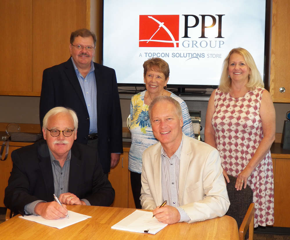 Jamie Williamson of Topcon with (clockwise from lower left) Tigue Howe, Jeff Peterson, Joan Peterson and Jean Howe of PPI Group during the signing event.