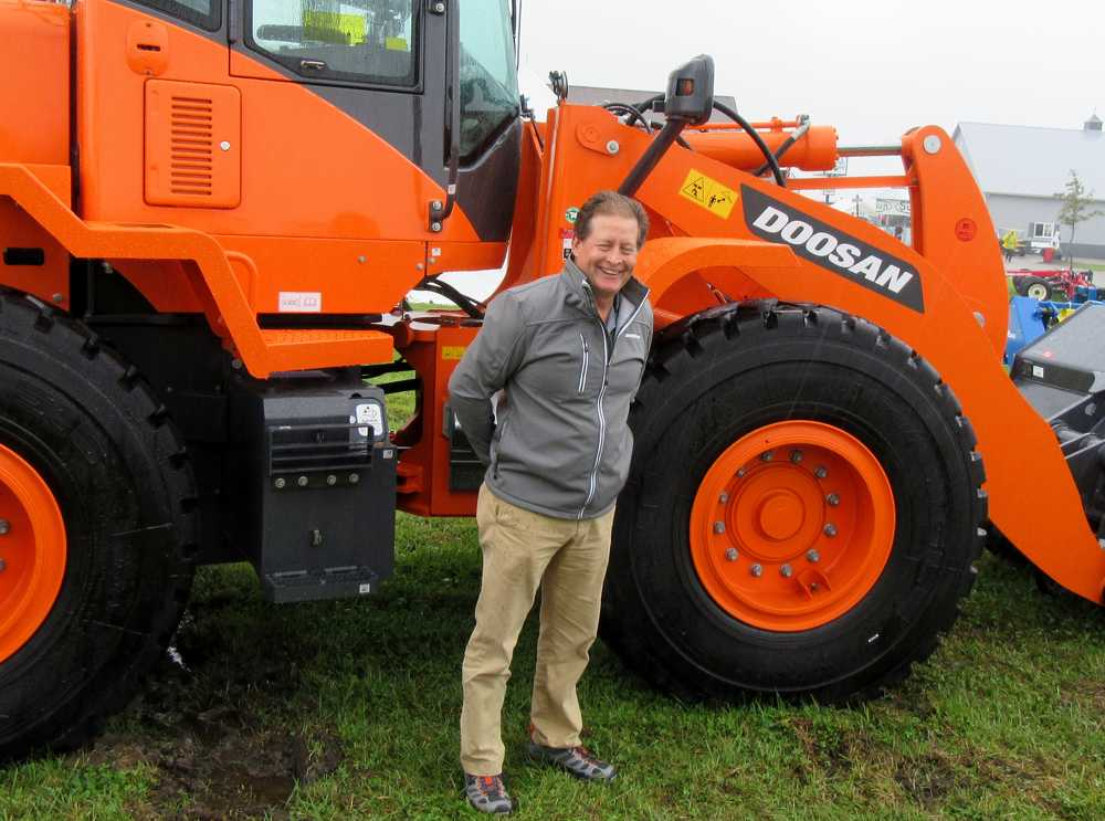 Marty Grace, Bobcat Enterprises' Doosan heavy equipment territory manager, braves the rain to talk about the equipment at the show.