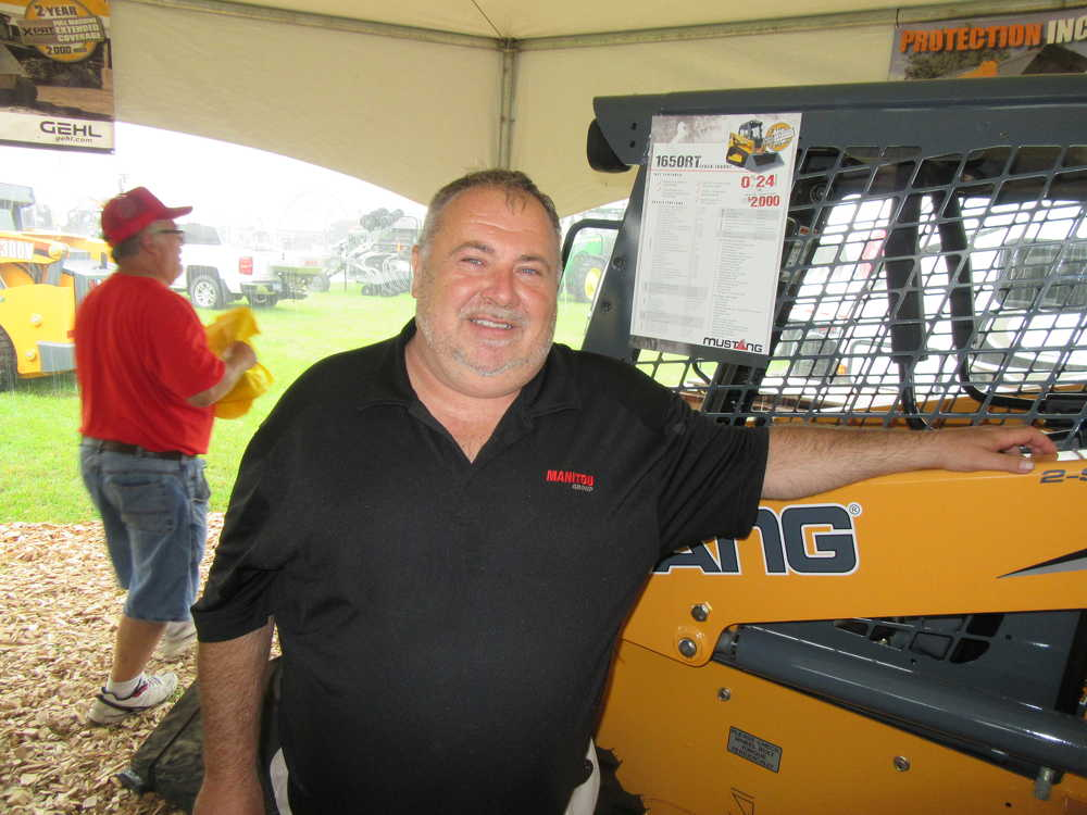 John Rau, Manitou product and training specialist, welcomes attendees to come in out of the rain to talk about the company's Manitou telehandlers, along with Gehl and Mustang skid steer loaders.