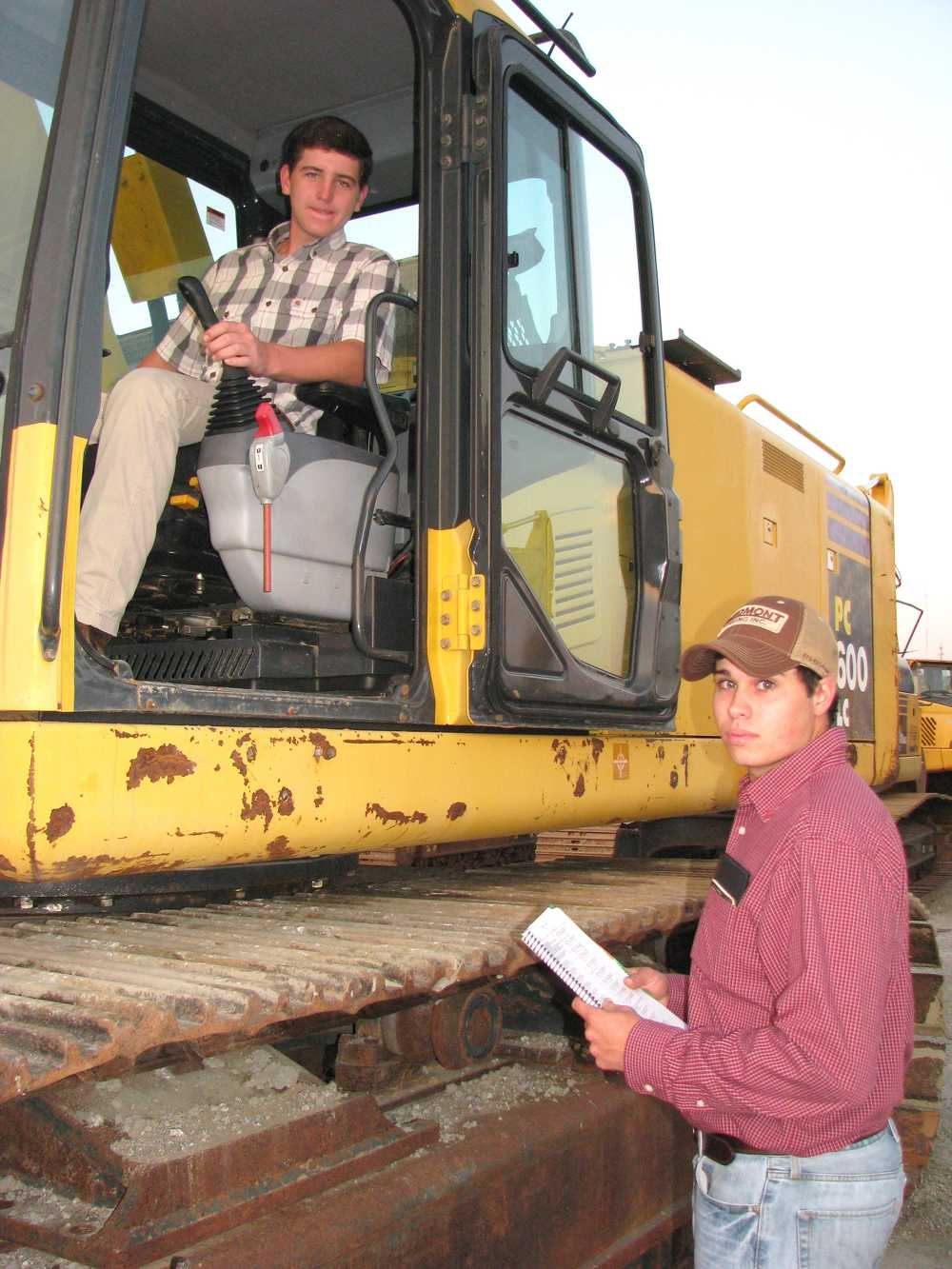 Cole Caldwell (L) and Andrew Loggins, both of  Piedmont Paving, Newnan, Ga., check out a Komatsu PC600LC excavator.