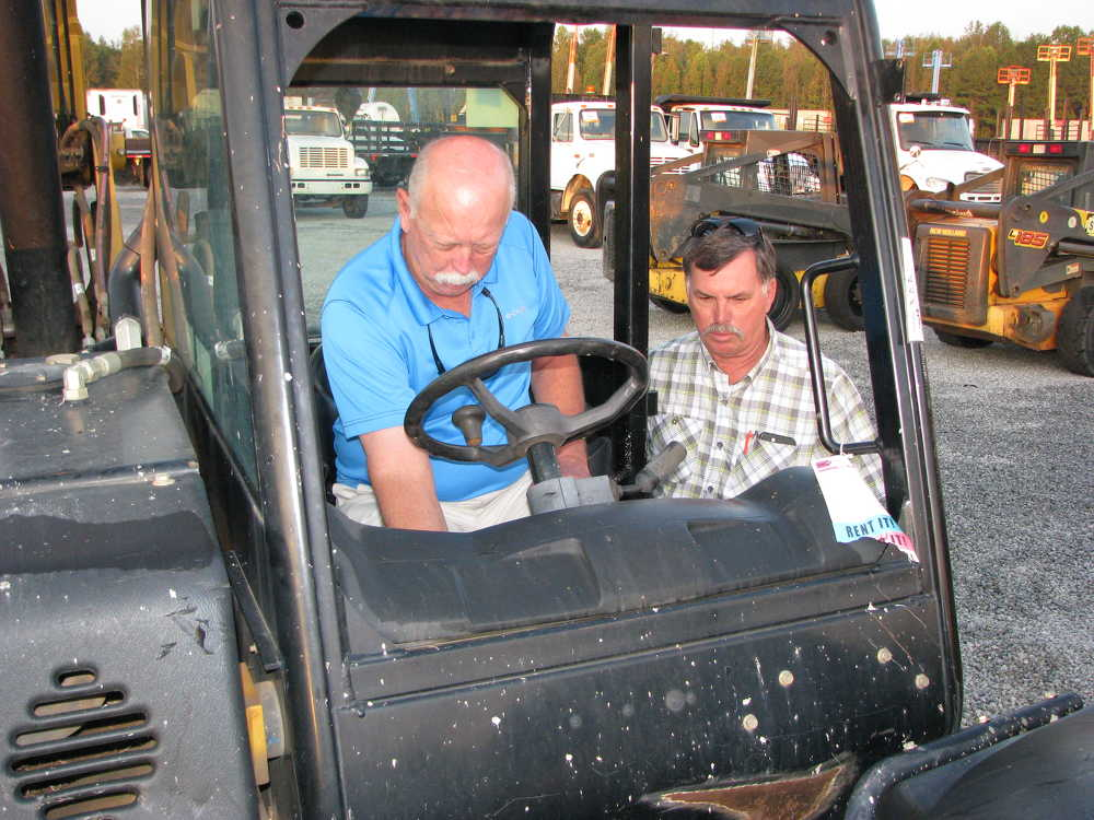 Randy Tidwell (L) and Steve Carter of Mid Georgia Electrical Services, Macon, Ga., look over this Cat TL642C reach forklift.