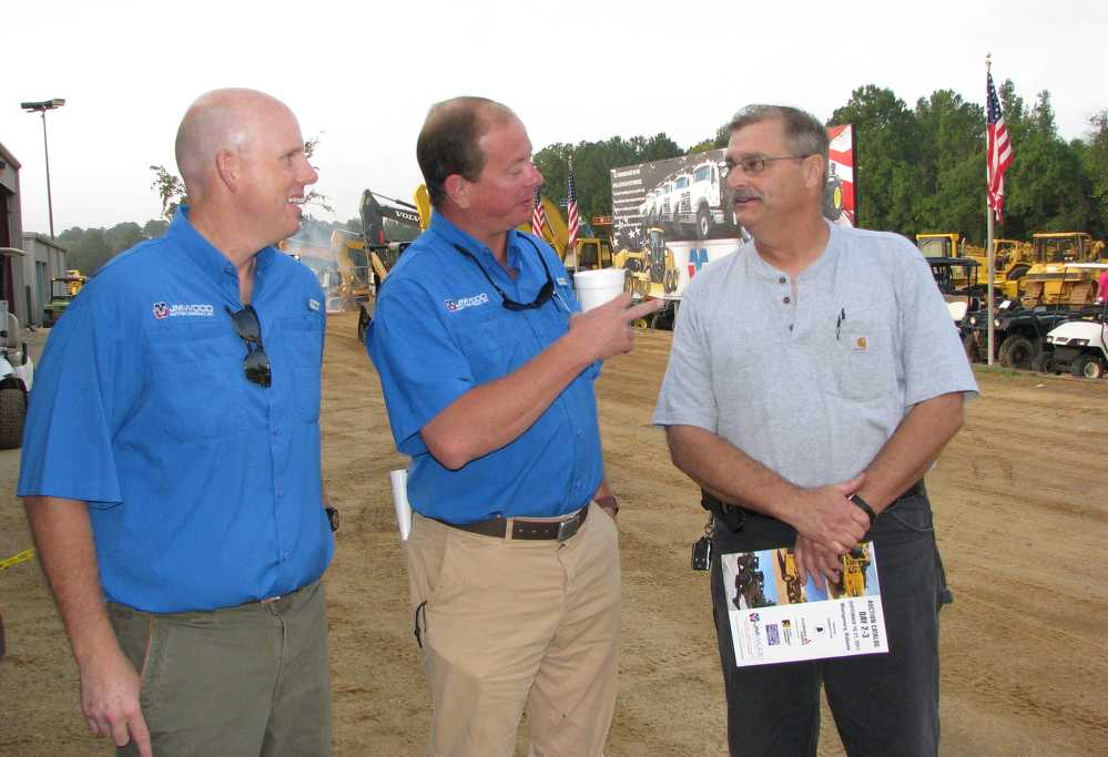 (L-R): JM Wood's Russ Wood and Curt Brown talk with Mark Guin of Scott Bridge Company, Opelika, Ala., about the machines on the block.
