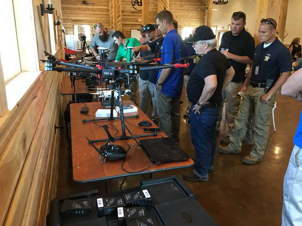 Guests look over different UAV that will be flown during the event. Platforms on table include: Matrice 600 Pro, modified to hold a cargo hook; a Phantom 4 Pro, modified to carry a FLIR camera; a Matrice 100 aerial mapping platform; and a SmartPlanes fixed wing drone.