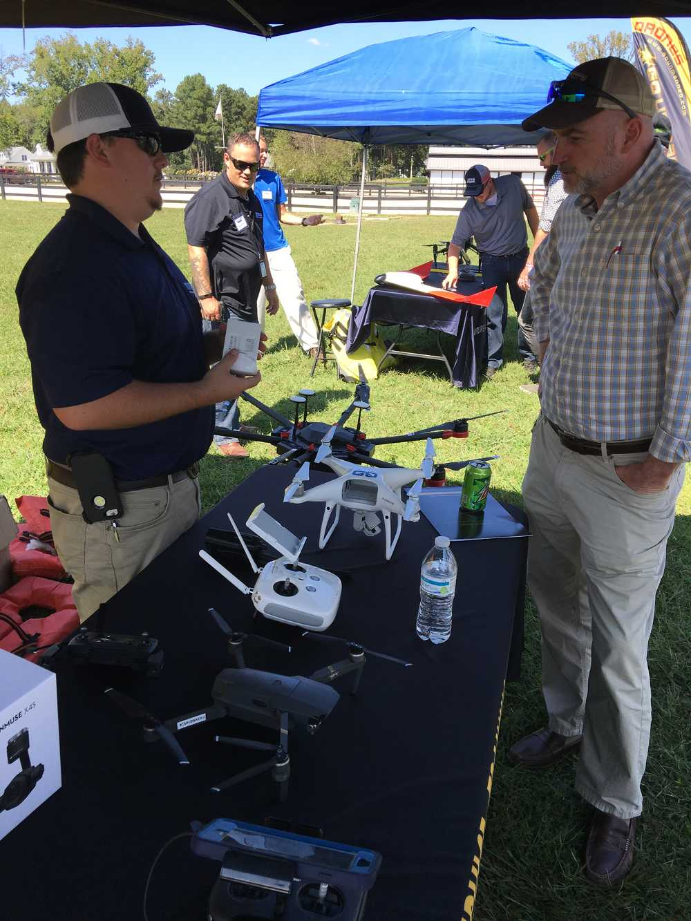 Mark Adams (L) talks with Tim Farley of Tim Farley Grading about the additional capabilities of the Phantom 4 Pro when paired with mapping software like DroneDeploy.