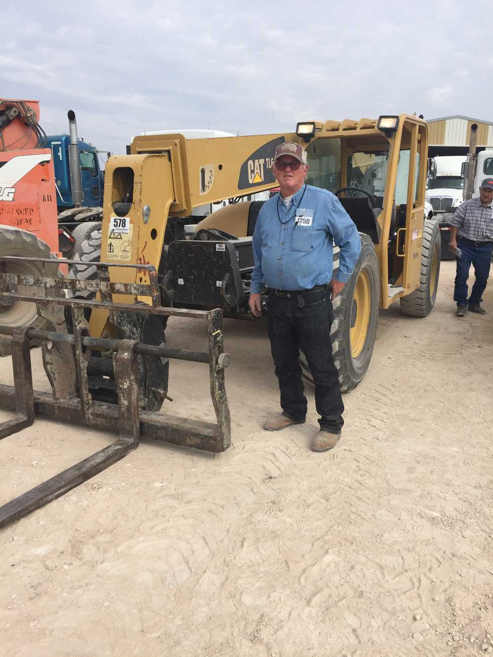 Lonnie Burcham, of Midland, Texas, looks over this 2007 Caterpillar TL642 telescopic forklift for sale in Stanton, Texas, on Sept. 13.