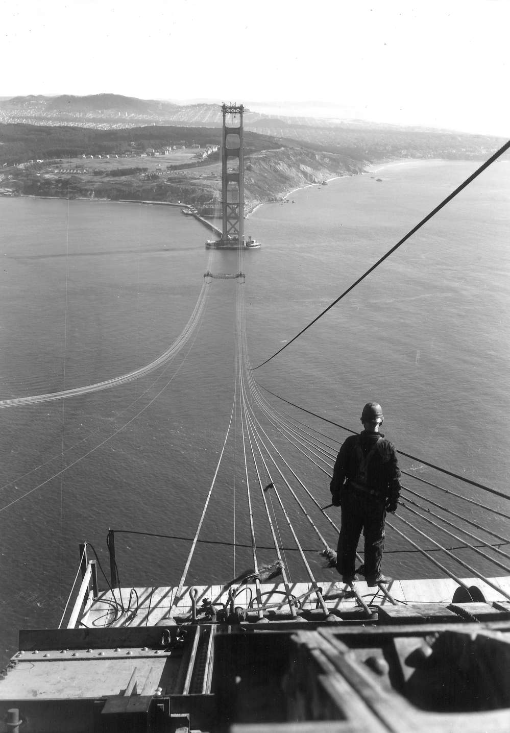 A worker pauses on the north tower during construction of the Golden Gate