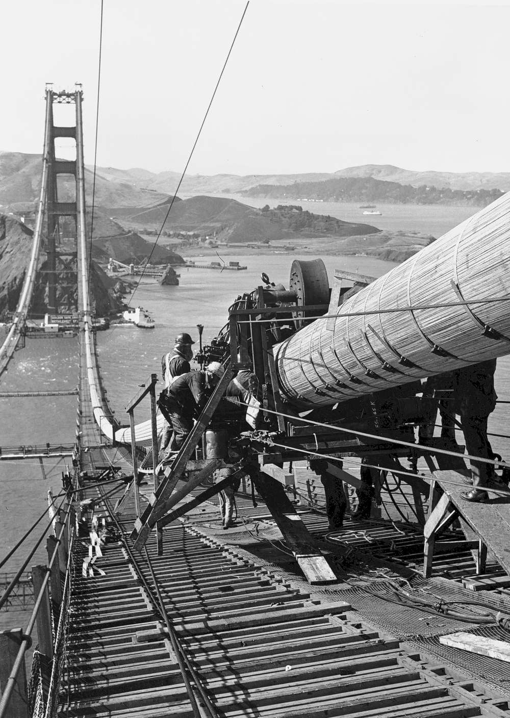 Cable is wrapped in 1935. A total of 80,000 mi. (128,747 km) of wire was used in the two main cables passing over the tops of the towers. (Fleet Irvine Photomurals/Photo)
