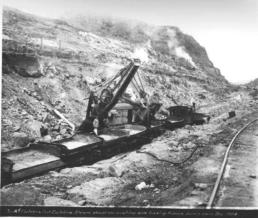 A steam shovel excavates and loads French dumb cars in December 1904 at the Culebra Cut.