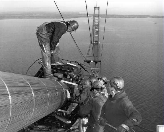 Workers checking the diameter of the east cable during compacting. Picture taken near the top of the south tower.