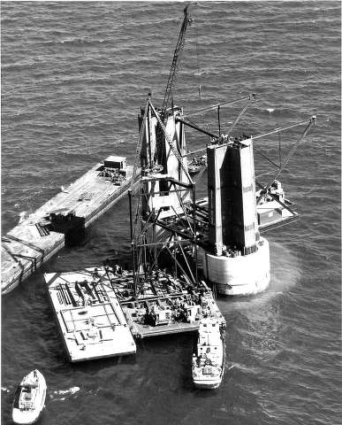 Crews erecting the creeper derrick on the south tower of the Mackinac Bridge. The creeper derrick was used to hoist the sections of the tower to their appropriate position.
