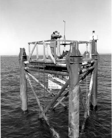 Two members of the survey crew work on Survey Tower No. 1 in the Straits of Mackinac during the placement of the foundations.