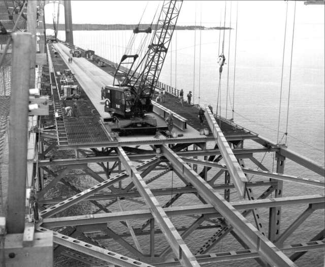 An American Bridge Division crane lifts a roadway stringer into position as other bridge- men install curbs, railing, and put finishing touches on roadway grating in 1957.